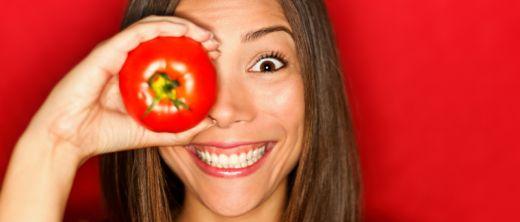 Hübsche Frau hält sich Tomate vors Auge