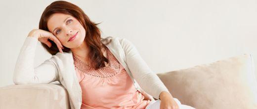 Frau sitzt auch Couch und lächelt